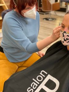 White woman sitting in a barber's chair receiving ear seeds